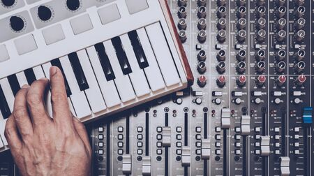 musician hand playing midi keyboard on audio mixing console Standard-Bild - 138449320