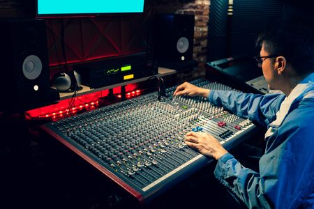 asian professional producer, sound engineer working on audio mixing console in recording, broadcasting studio