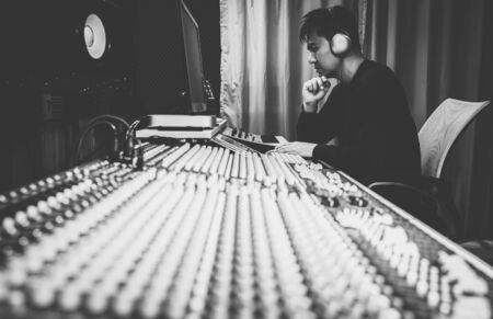 asian male professional music producer, sound engineer, composer, arranger working on audio mixing console in home recording studio. black and white. post production and broadcasting concept Stock Photo