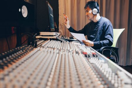 asian young male professional music producer, sound engineer, composer, arranger working in home recording studio. post production and broadcasting concept Stock Photo