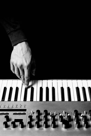 male musician hand playing music keyboard synthesizer, black and white. music background