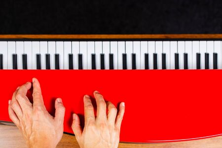 male musician hands enjoy practicing piano lesson on red piano lid, music background