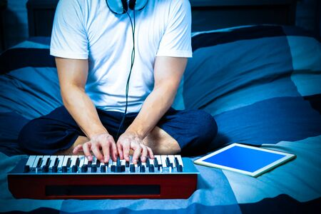 man learning online music lesson and playing keyboard on bed in bedroom at night Stock Photo