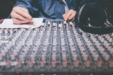 male professional songwriter, producer writing a song on audio mixing console in recording studio