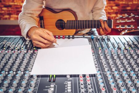 male songwriter playing acoustic guitar and writing a song on audio mixing board in sound studio Stock Photo