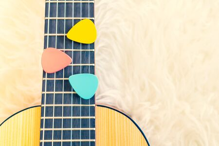 colorful pick on small acoustic guitar fretboard. music background Stock Photo