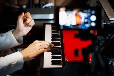 music vlogger streaming a live video while playing piano in home studio Stock Photo
