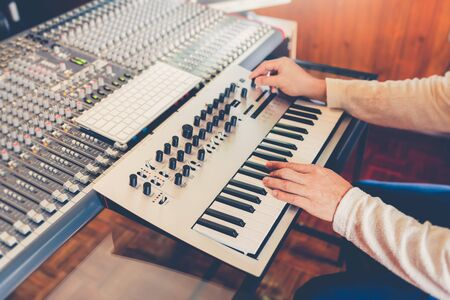 male professional producer, composer designing sound for movie music score in recording studio