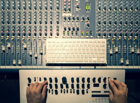 top view of male sound engineer hands tweaking knobs for editing, designing sound on synthesizer and audio mixing board in studio. sound design concept Stock Photo
