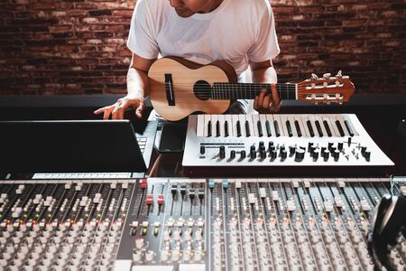 asian male songwriter playing acoustic guitar for making music on computer in home recording studio