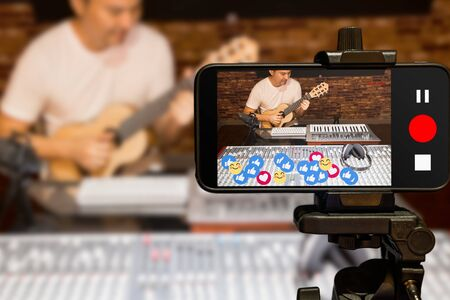 music vlogger streaming a live video while playing acoustic guitar in home studio Stock Photo