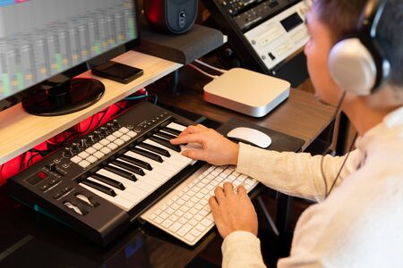 asian man learning online music production technology on computer and midi keyboard from internet in home studio