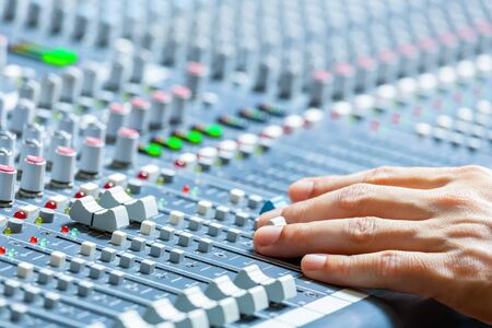 male sound engineer hands working on audio mixing console. broadcasting, recording concept