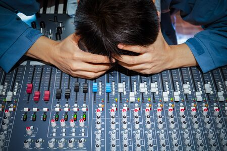 asian male music producer, dj, sound engineer feel disappointed at bad sound in studio. music production, recording,  broadcasting, post production concept