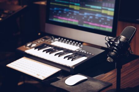 microphone, keyboard, computer on desk in home studio. music production concept Stock Photo