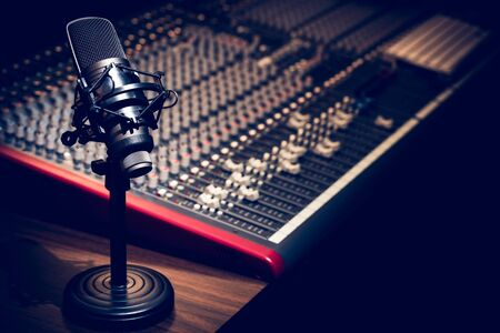condenser microphone on audio mixing console background Stock Photo
