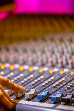 sound engineer fingers adjusting on audio mixing console fader. recording, broadcasting concept