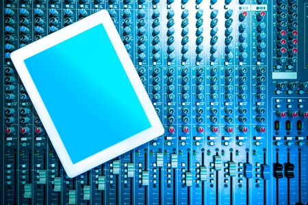 blank tablet computer on audio mixing console Stock Photo