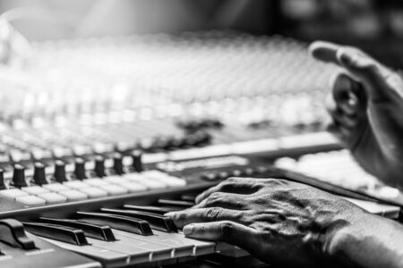 composer hands on piano keys in recording studio