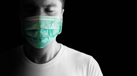 asian man at risk of infection in coronavirus covid 19 wearing mask on black background