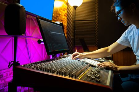 asian male sound engineer mixing music on audio mixing console in recording studio
