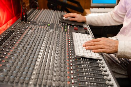 professional male producer, sound engineer hands working on computer and audio mixing console in recording, editing, broadcasting studio. post production concept