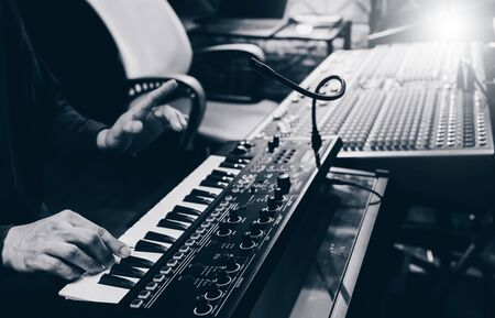 musician hands playing keyboard synthesizer for recording in home recording studio Stock Photo