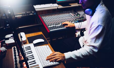 male music producer, composer arranging a song in home recording studio. music production technology concept