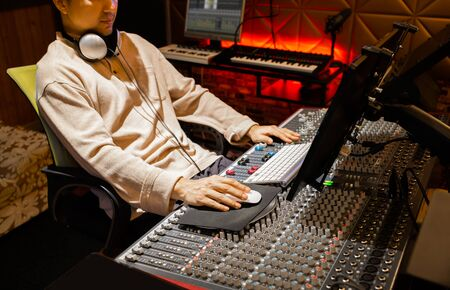 Asian male producer, sound engineer working on computer and mixing console in recording studio. Stock Photo