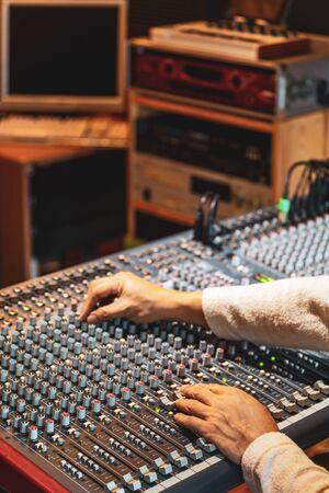 Manos del ingeniero de sonido trabajando en la consola de mezcla de audio en el estudio de grabación, radiodifusión