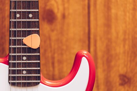 pink pick on electric guitar fretboard Stock Photo