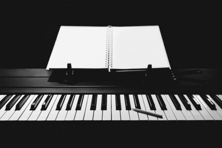 song writing concept. pencil on piano keys with blank white music sheet