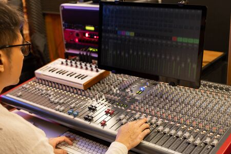 male sound engineer, producer, composer mixing music on audio mixer in recording studio