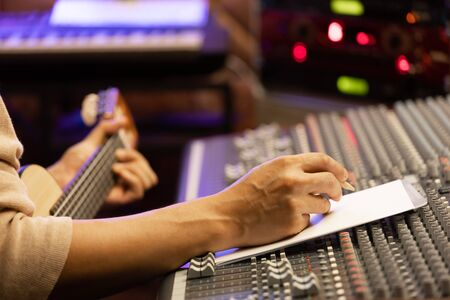 male artist, songwriter writing a song on white paper in recording studio