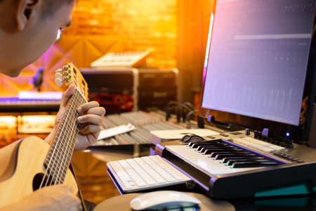 asian man learning acoustic guitar lesson from internet in sound studio