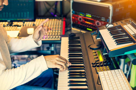 male musician, producer, composer playing electric piano in home studio 免版税图像