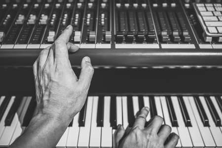 male musician hands playing on piano keys. black and white Banque d'images