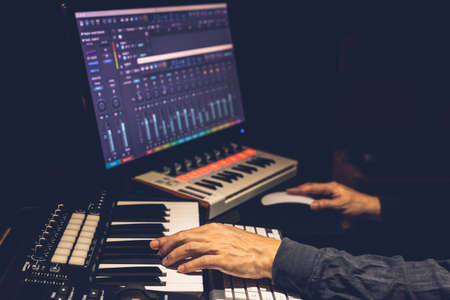 music producer hands arranging a song on midi keyboard and computer in studio. music production concept