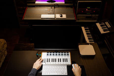 top view of male music producer hands working on midi keyboard and computer in recording studio