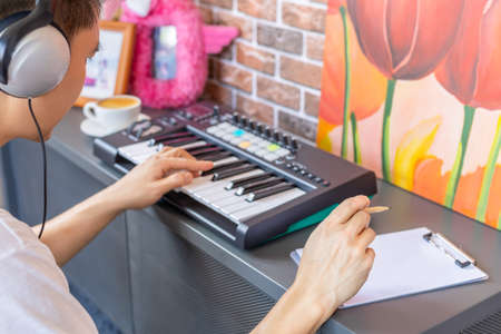 asian male songwriter playing keyboard and writing a song on white music sheet in modern loft living room Standard-Bild