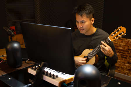 asian handsome male music vlogger streaming a live video while playing acoustic guitar at home or online e-learning music lesson