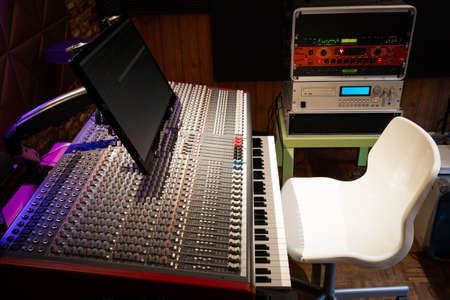audio mixing console, blank white chair and sound processing equipment in recording studio