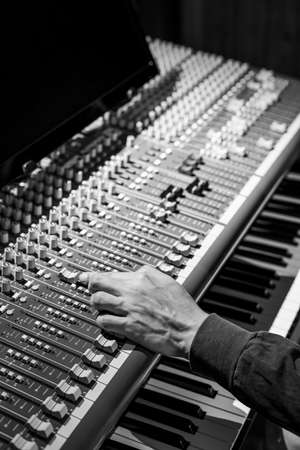sound engineer hand adjusting level fader on audio mixing console in studio