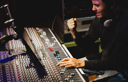 happy asian sound engineer finished his work in broadcasting, recording studio