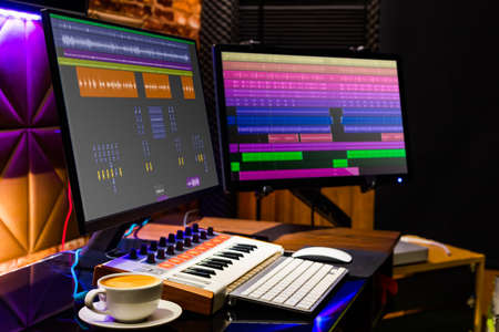 cup of coffee on desk with dual display monitor and midi keyboard for music production Standard-Bild