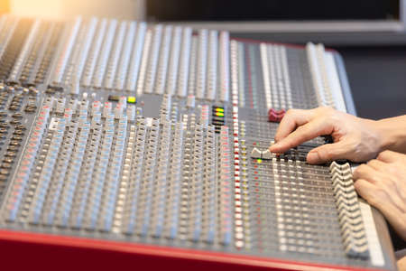 professional sound engineer hands adjusting audio input signal on mixing console in broadcasting, recording studio 版權商用圖片