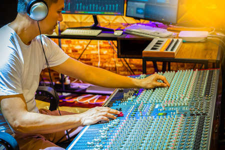 asian producer, sound engineer adjusting equalizer on audio mixing console in recording studio