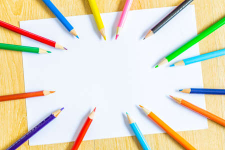 colorful pencils on white paper for education, art background