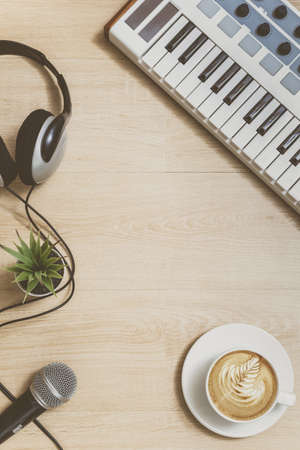 piano, cup of coffee, headphone, microphone and plant on wooden floor. film look. relaxation concept