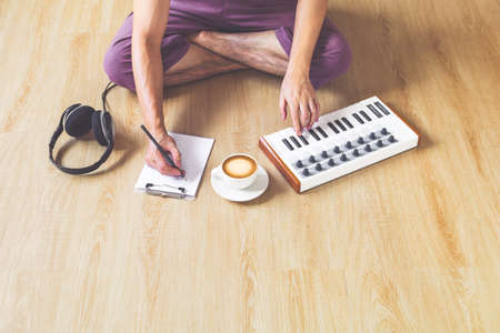male songwriter playing music keyboard and writing a song on wooden floor. song writing concept Standard-Bild